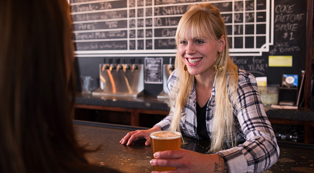 Woman serving a customer a craft beer at a bar counter.