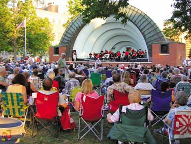 Concert-goers sitting in lawn chairs at Bandshell Park