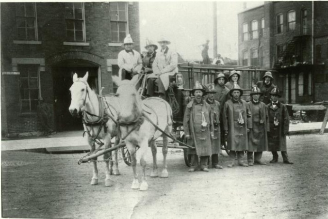 Historic photo of firefighters standing in front of and sitting on a horse-driven hose cart.