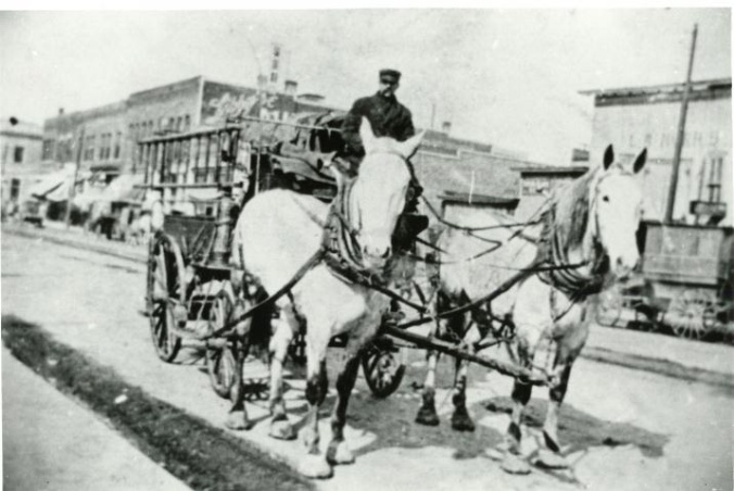 Circa 1915photo of a horse-driven hose cart going down the street.
