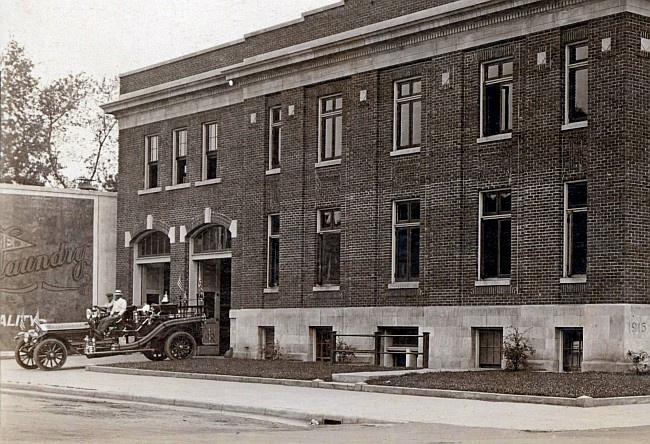 1921 City Hall with a small motorized fire engine pulling out through the overhead door.