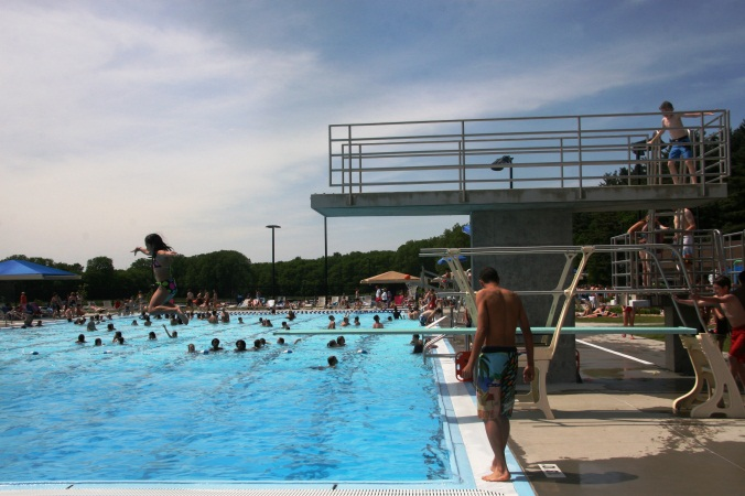 A child standing near the diving board at the Furman Aquatic Center