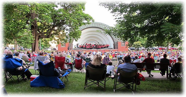 A large group of concert-goers in lawn chairs at Bandshell Park