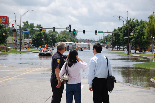 Ames Police Officer speaking with residents in front of flooded S. Duff in the Flood of 2008
