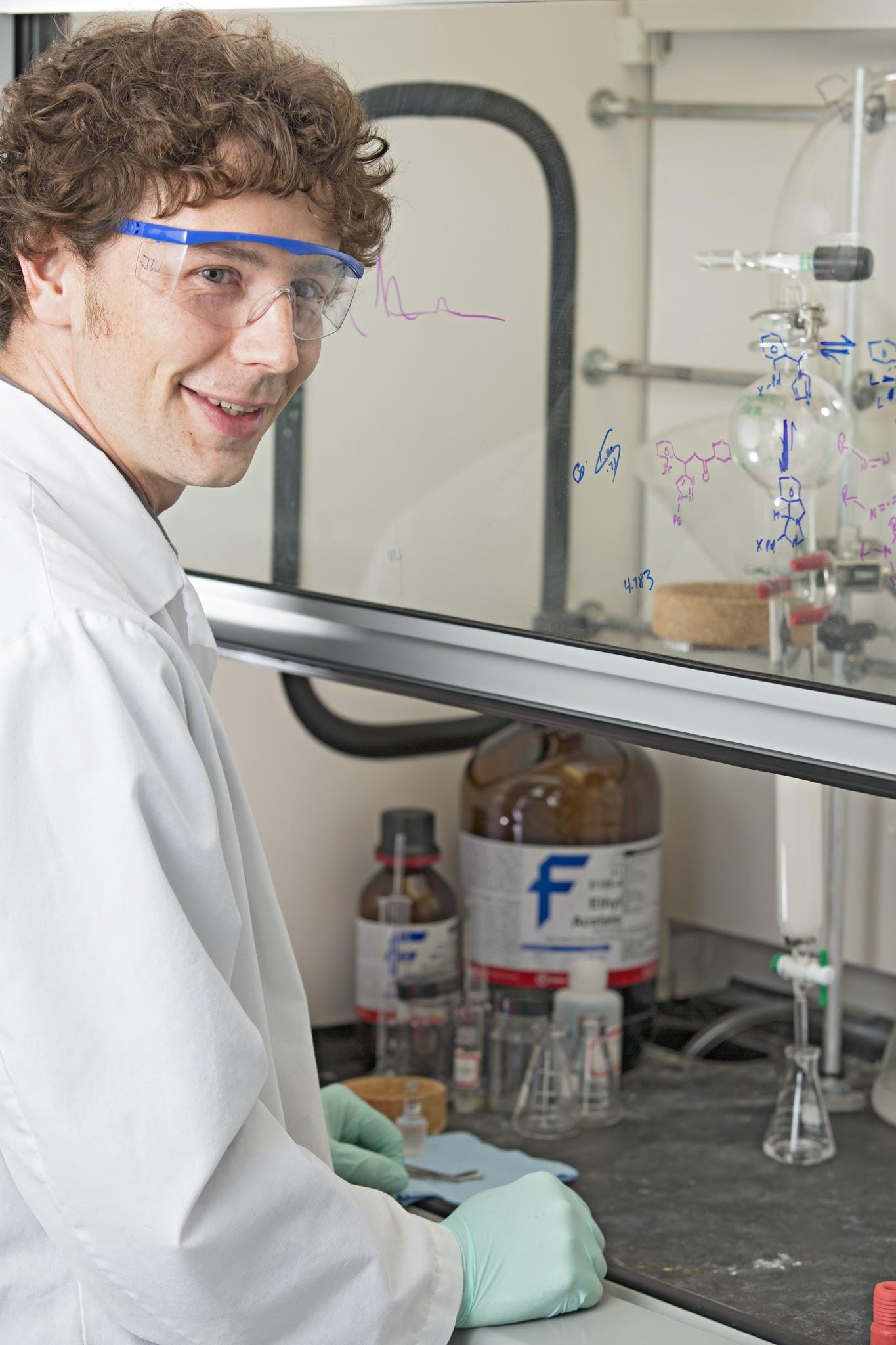 Person in a lab coat and safety glasses with bottles of chemicals & science equipment in the background